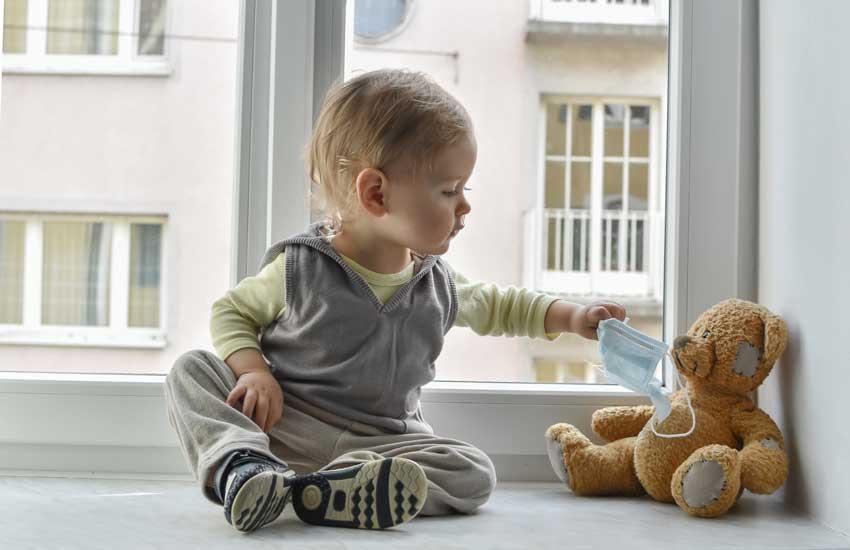 Kleinkind legt Teddy Atenschutzmaske an
